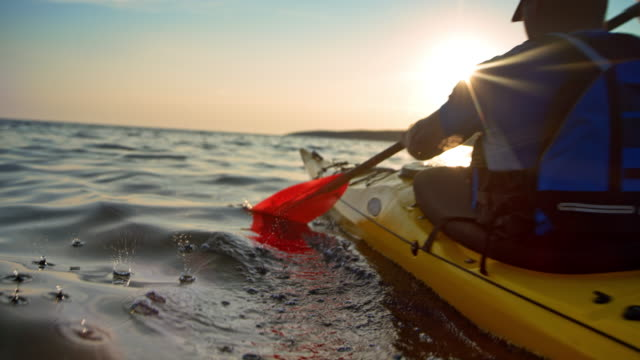 SLO MO Man in a yellow sea kayak passing by in sunshine
