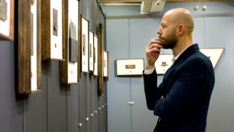 vídeos de stock e filmes b-roll de man in art gallery - arte