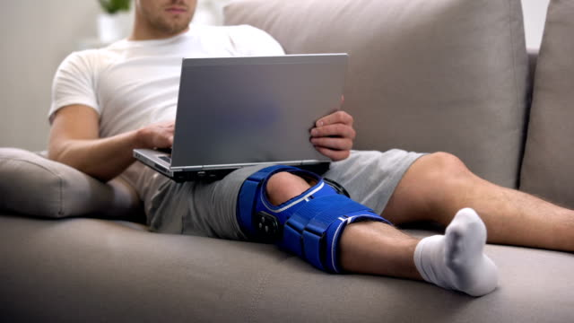 Man in arthritis knee brace working on laptop at home rehab period and freelance Man in arthritis knee brace working on laptop at home rehab period and freelance physical injury stock videos & royalty-free footage