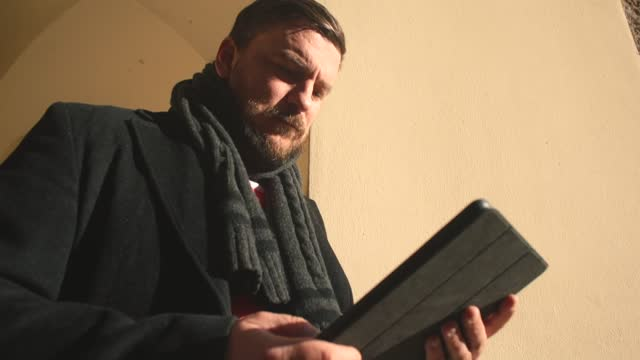 Man in autumn sunlight monitors news, using tablet with weather forecast app.