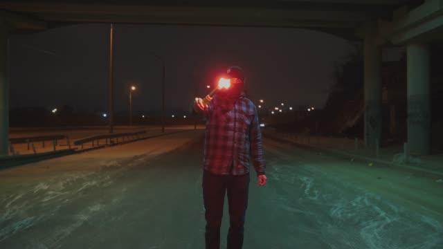 赤く燃えてる夜信号炎管と目出し帽の男 - street graffiti点の映像素材/bロール