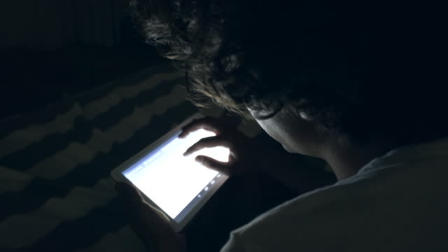 stockvideo's en b-roll-footage met man in bed surfen op het internet op een tablet. - onherkenbaar persoon