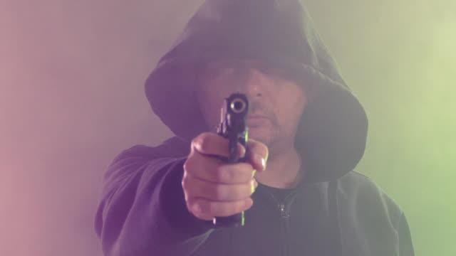 man in black hoodie points handgun in colored haze of smoke - top nero video stock e b–roll