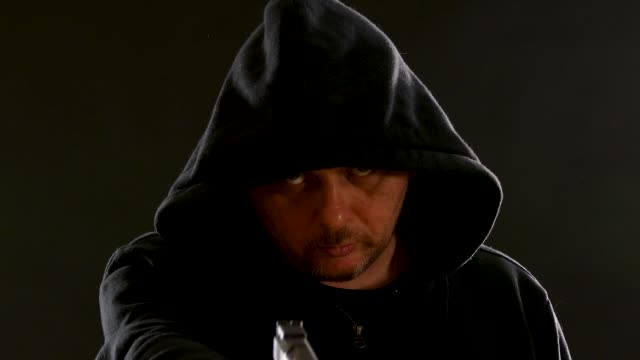 man in black hoodie points pistol - top nero video stock e b–roll