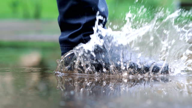 vídeos de stock e filmes b-roll de man in black shoes stepping into the puddle in 4k slow motion 60fps - poça