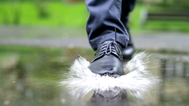 man in black shoes stepping into the puddle in slow motion 180fps - fare un passo video stock e b–roll