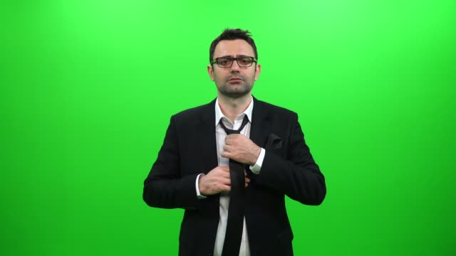 man in black suit tying a tie on a green background - затягивание стоковые видео и кадры b-roll
