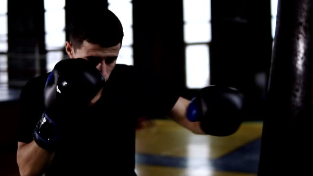 Man in black T-shirt, determinated boxer making strikes on a boxing bag indoor in the gym. Fighter training alone in slow motion