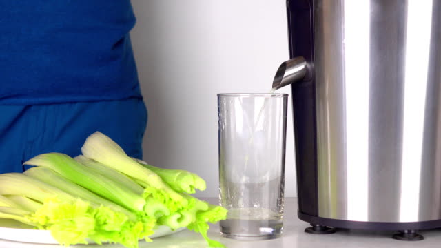 man in blue clothes making green celery juice on polished juicer. fullhd shot - sedano video stock e b–roll