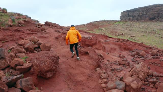 4k uomo in cappotto sportivo arancione brillante che attraversa terreni rocciosi di argilla - canyon video stock e b–roll