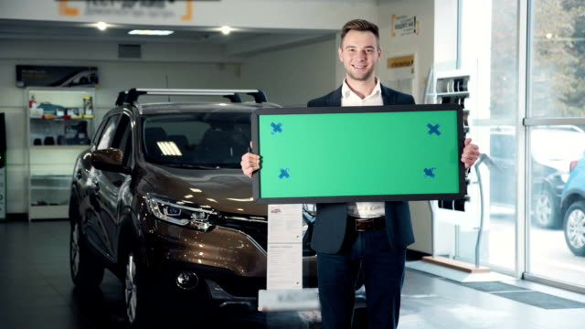 Man in Car Dealership Holding Green Sign Three Quarter Length Portrait of Smiling Man Wearing Checkered Shirt Standing inside Car Dealership in front of Shiny New Vehicle and Holding Blank Green Sign with Copy Space. FullHD car salesperson stock videos & royalty-free footage