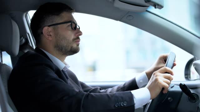 stockvideo's en b-roll-footage met man in de auto lijdt aan visie problemen met het in-en uitschakelen van brillen, gezichtsvermogen - bril brillen en lenzen
