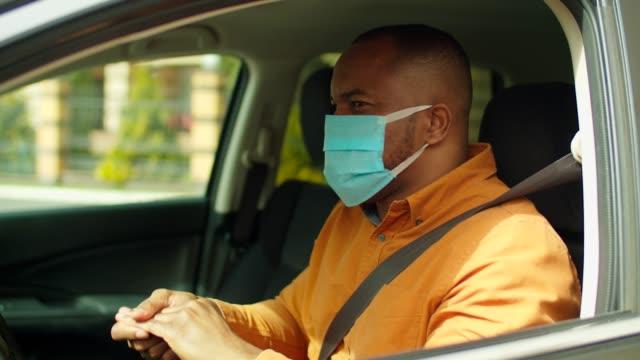 vídeos de stock, filmes e b-roll de homem no carro usando desinfetante para as mãos para prevenir infecção - consciência negra