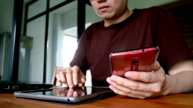 mannen i casual kläder använder digitala tablett dator, mobiltelefon och bärbar dator i vardagsrummet - mobil teknik kommunikationskoncept - telefonmeddelande bildbanksvideor och videomaterial från bakom kulisserna