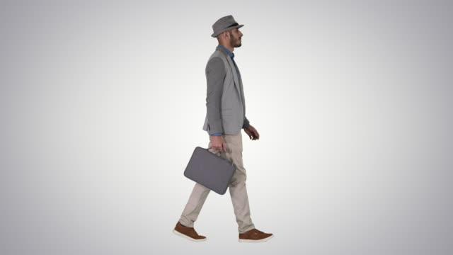 グラデーションの背景にブリーフケースを持つカジュアルな歩行中の男性 - 全身点の映像素材/bロール