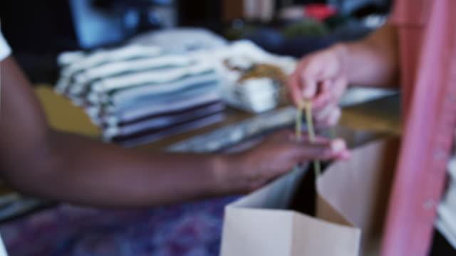 uomo nel negozio di abbigliamento che effettua pagamenti contactless al banco vendite con orologio intelligente al lettore tenuto dall'assistente alle vendite maschile - girato al rallentatore - computer indossabile video stock e b–roll
