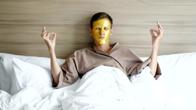 man in coat with golden face mask meditates in bed in hotel