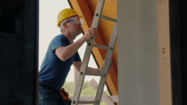stockvideo's en b-roll-footage met man in construction site, manual worker on ladder using hammer - ladder