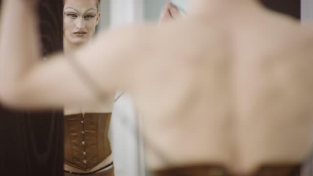 stockvideo's en b-roll-footage met man in slepen zetten korset - drag queen