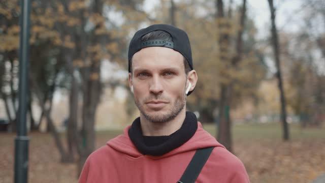 uomo in auricolari e felpa con cappuccio rosso, berretto nero sullo sfondo degli alberi del parco cittadino - berretto video stock e b–roll