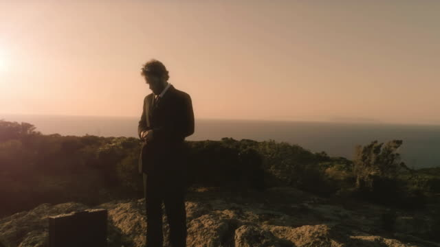 Man in elegant suit straightens his jacket on top of a cliff on an island video