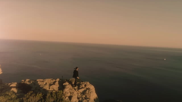 Man in elegant suit with briefcase exulting on top of a cliff on an island video