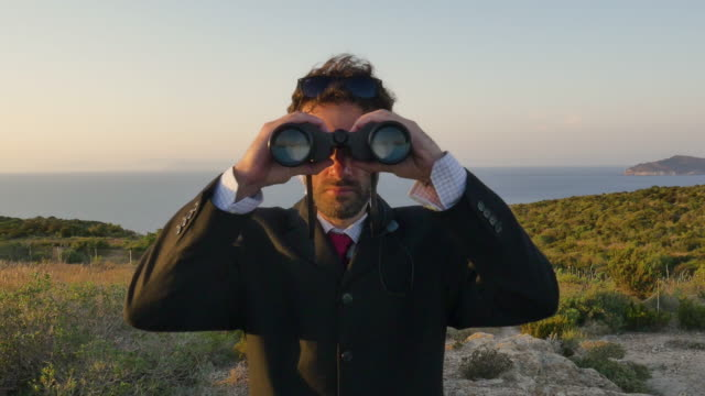 Man in elegant suit with briefcase looking through binoculars on top of a cliff on an island