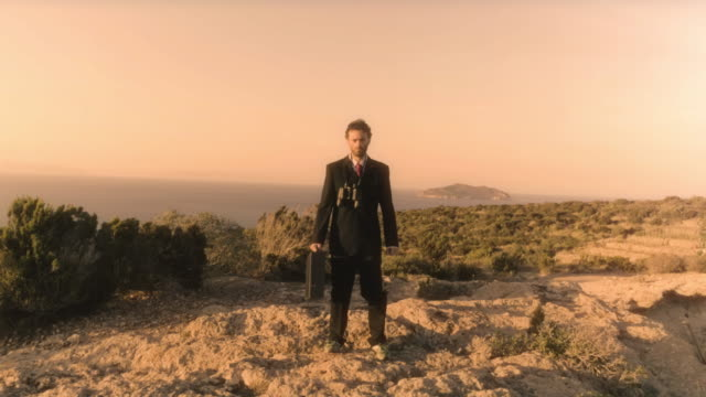 Man in elegant suit with briefcase looking through binoculars on top of a cliff on an island video