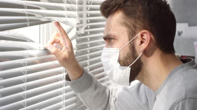 człowiek w masce zaglądając przez rolety okienne - store filmów i materiałów b-roll