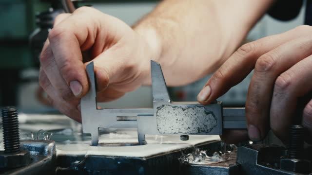 Man in factory measure  hole in steel with vernier caliper.