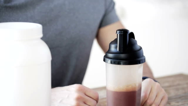 man in fitness tracker with jar and bottle preparing protein shake video