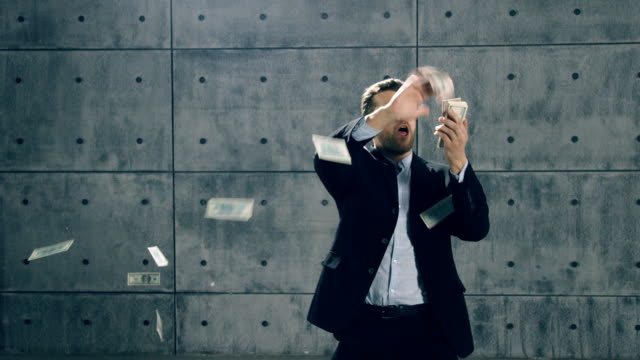 man in formal suit dancing and throwing money - risparmi video stock e b–roll