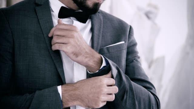 vídeos de stock, filmes e b-roll de homem no terno formal que começ vestido no camarim para o trabalho ou o casamento. - punho