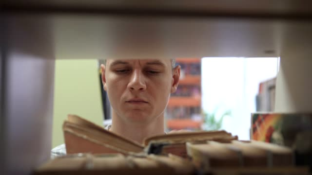 A man in front of a bookcase in a library chooses a book - vídeo