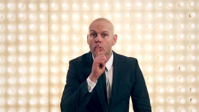 vídeos y material grabado en eventos de stock de man in front of lightwall - dedo sobre labios