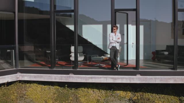vídeos de stock e filmes b-roll de man in front of luxury building - mansão imponente