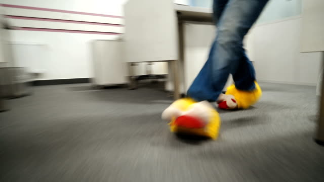 Man in funny yellow slippers walks around the office. Male feet close-up walking through the office. video