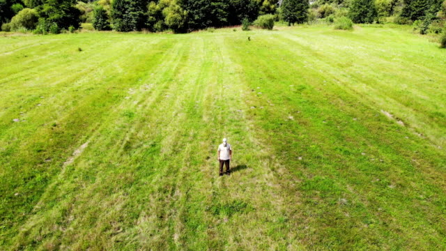 man in gas mask outdoors not able to breath, out of oxygen, in green meadow, surreal, disaster concept, arial shot from drone