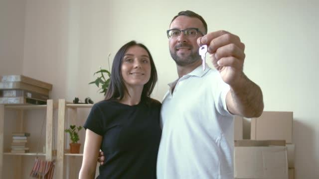 stockvideo's en b-roll-footage met een man in bril en een wit t-shirt knuffels zijn dark-haired vrouw, die hem hugs. in de handen van de man houdt de toetsen naar het nieuwe appartement op de wijsvinger - wit t shirt