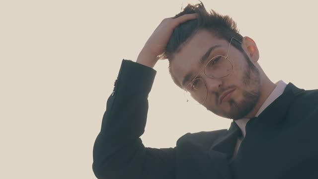 man in glasses fixes hair waving in wind slow motion stylish young man in modern glasses and office suit fixes hair waving in wind against sunset extreme closeup slow motion businesswear stock videos & royalty-free footage