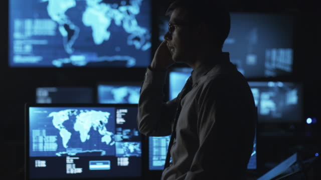 Man in glasses is talking on the phone in a dark monitoring room filled with display screens. video