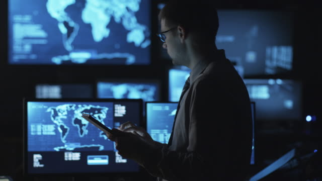 Man in glasses is using a tablet computer in a dark monitoring room filled with display screens. video