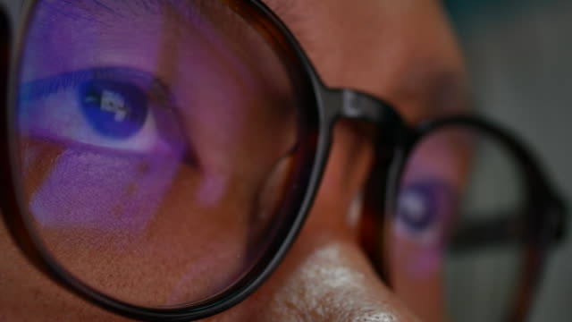 Man in glasses reflection surfing internet at night video
