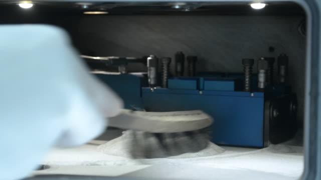 Um homem em luvas limpa a câmara de trabalho com uma escova de um pó de metal - vídeo
