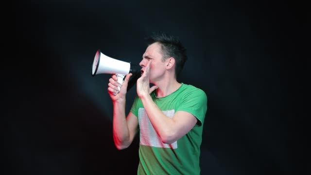 A man in green clothes shouts in a megaphone on a black background.