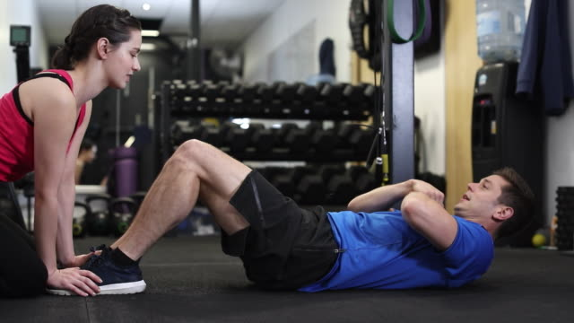 Man In Gym Doing Sit Ups Encouraged By Personal Trainer video