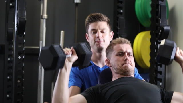 Man In Gym Lifting Dumbbells Encouraged By Personal Trainer video