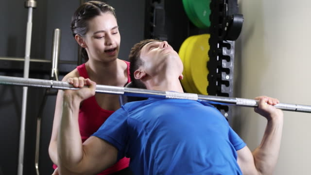 Man In Gym Lifting Weights On Bar Encouraged By Personal Trainer video