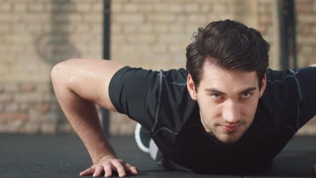 Man in gym making push-ups Man wearing sports outfit making push-ups in a gym gym. push ups stock videos & royalty-free footage