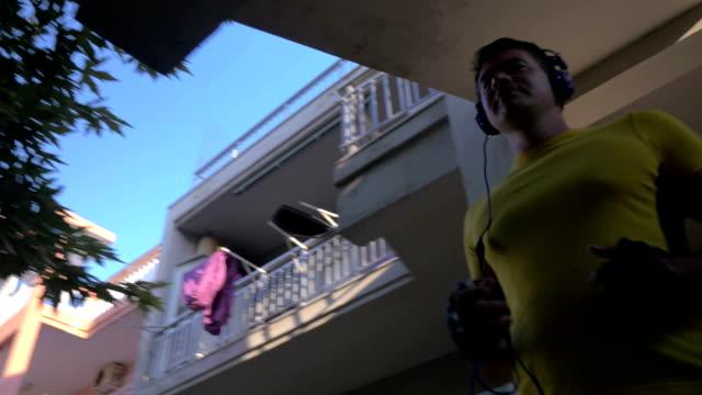 człowiek w słuchawki i odzież sportowa pozostawiając hotel - sportowiec filmów i materiałów b-roll